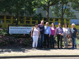 Fotografia do grupo de participantes na visita a Düren, junto ao cartaz que anuncia o Centro BFW