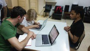 Fotografia de dois participantes e um tutor a trabalharem com MacBook