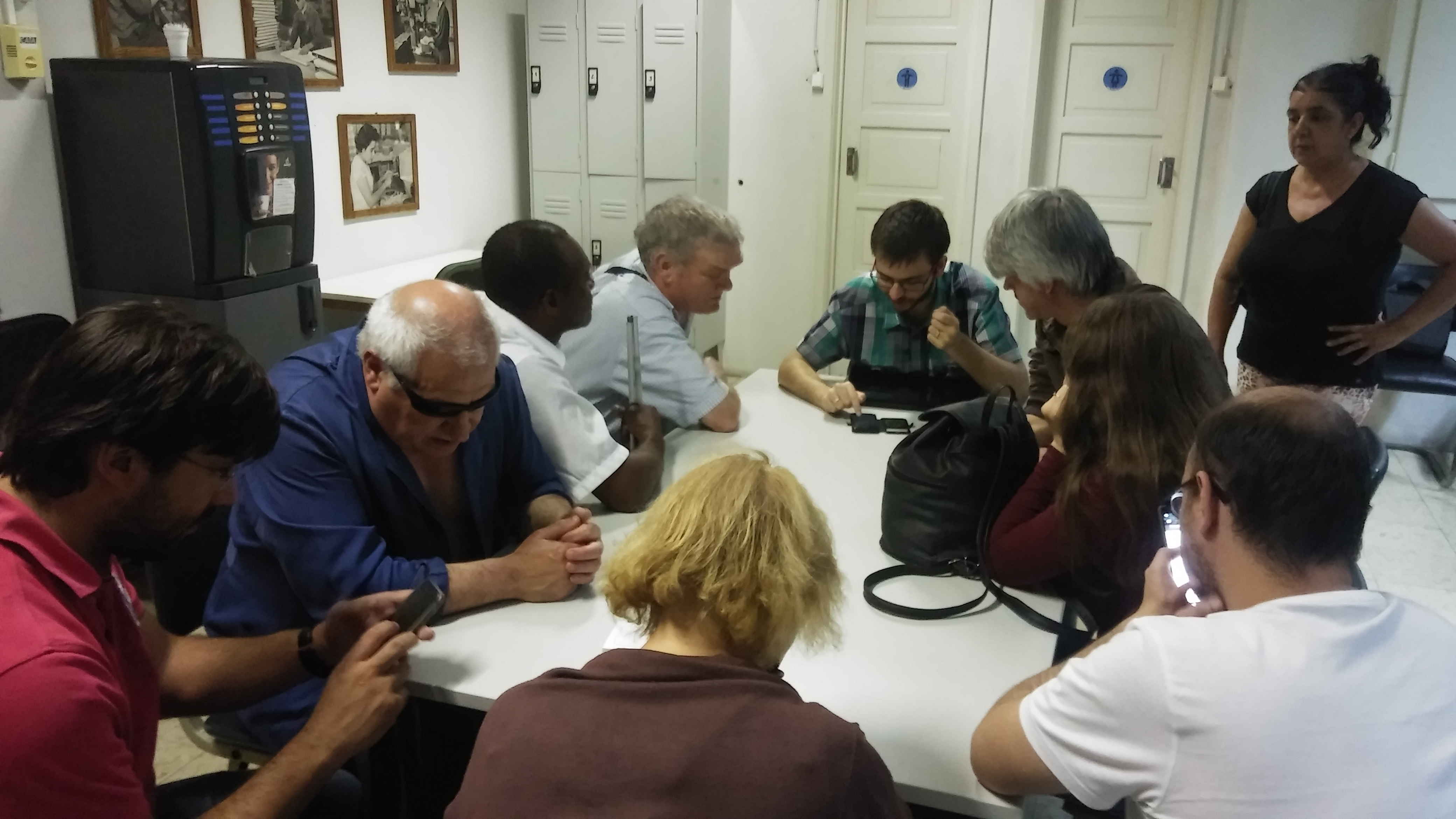 Fotografia geral do grupo de participantes na mesa onde se trabalhava com dispositivos Iphone