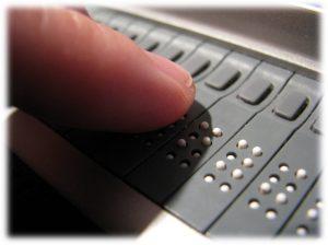 Fotografia de pormenor de um dedo sobre uma linha braille